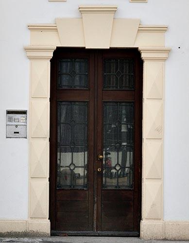 cornice portone ingresso con profili bugnati e chiave di volta